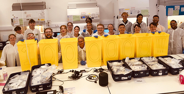 Volunteer researchers celebrating the processing of one million tests